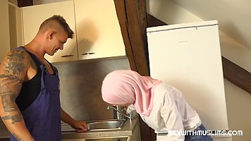 A Muslim woman seduced a plumber in uniform in the kitchen and pushed him before...