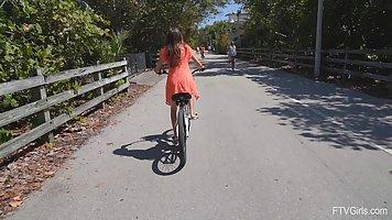 Во время прогулки на велосипеде девушка показывает свою попку