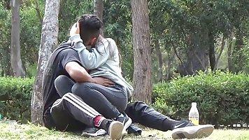 Парень с подругой на лужайке в парке записывают домашнее видео для взрослых